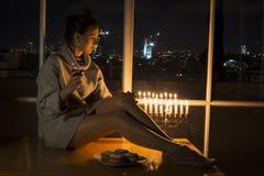 Uma menina senta-se pela janela com o menorah que comemora o Hanukkah Foto de Stock