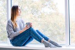 Uma menina senta-se perto de um grande chá da janela e das bebidas fotografia de stock