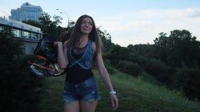 Uma menina 'sexy' atravessa o parque, vestindo sapatas especiais dos saltos do angoo em suas mãos 4K mo lento filme