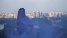 Uma menina 'sexy' com o fumo azul que dança graciosamente na perspectiva do fumo 4K mo lento filme