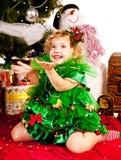 Uma menina sob a árvore de Natal com presentes Foto de Stock