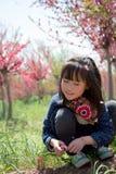 Uma menina sob as flores do pêssego Foto de Stock