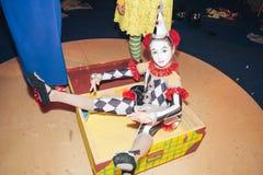 Uma menina sob a forma do arlequim, sentando-se em uma mala de viagem que descreve a figura congelada de uma boneca foto de stock