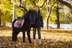 Uma menina, suportes ao lado de um pônei preto bonito em um outono estaciona imagens de stock royalty free