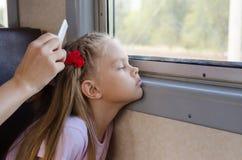 Uma menina triste olha a janela quando se sentar em um trem bonde até minha mãe pentear seu cabelo longo Fotos de Stock Royalty Free