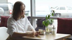 Uma menina usa um telefone celular que senta-se em um café uma jovem mulher envia uma mensagem com telefone celular e café bebend vídeos de arquivo