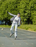 Uma menina vai nos patins de rolo, tentando manter o equilíbrio Imagens de Stock Royalty Free