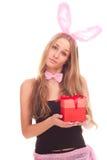 Uma menina vestida como um coelho com presentes Imagens de Stock Royalty Free