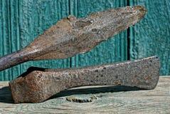 Uma mentira velha longa do machado da lança e da batalha do ferro em uma tabela cinzenta contra uma parede verde fotos de stock