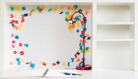 Uma mesa da escola do ` s da criança com um livro de nota do papel de gráfico, pena e lápis e um fundo branco com letras e número fotos de stock