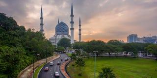 Uma mesquita e um nascer do sol nebuloso com os carros que movem sobre estradas Fotografia de Stock Royalty Free