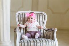Uma metade do ano da menina cuja um, 6 meses velho, no corpo bonito e na saia, com curva brilhante em uma cabeça Bebê de sorriso  Fotos de Stock Royalty Free