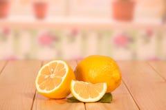 Uma metade e uma parte maduras do limão no fundo da cozinha Foto de Stock Royalty Free