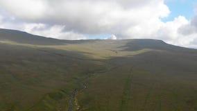 Uma metragem dianteira aérea de uma inclinação gramínea da cimeira majestosa da montanha com um córrego, um céu azul e umas nuven video estoque