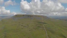 Uma metragem esquerda para a direita sideway aérea de uma montanha rochosa da cimeira com o trajeto verde da inclinação e da fuga filme