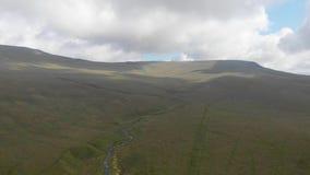 Uma metragem inversa aérea de uma inclinação gramínea da cimeira majestosa da montanha com um córrego, um céu azul e umas nuvens  video estoque