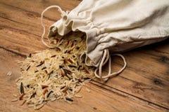 Uma mistura de grões do arroz em um saco dispersado em uma tabela de madeira foto de stock