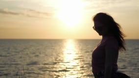 Uma moça admira o por do sol bonito pelo mar, sopros de um vento claro 4k, 3840x2160 HD video estoque