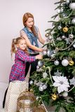 Uma moça ajuda sua mãe a decorar a árvore de Natal da família imagem de stock
