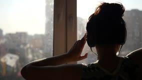 Uma moça alegre, suportes pela janela em seus fones de ouvido e danças no sol Slowmo 1920x1080 video estoque