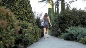 Uma moça anda em um parque verde bonito no verão com plantas e as árvores incomuns nave video estoque