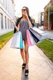 Uma moça aprecia uma compra bem sucedida, no fundo de fotos de stock