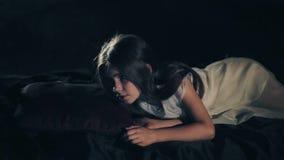 Uma moça bonita acorda Fundo escuro projeto social Cabelo longo Close-up Vestido branco confused feliz video estoque