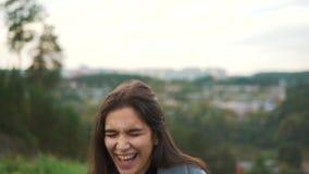 Uma moça bonita com cabelo longo é de riso e de vista a câmera Ande no parque, contra a cidade filme