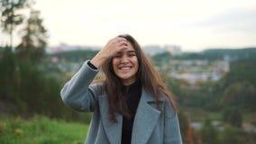 Uma moça bonita com cabelo longo é de riso e de vista a câmera Ande no parque, contra a cidade vídeos de arquivo