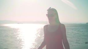 Uma moça bonita em um roupa de banho de uma peça só vermelho e em caminhadas dos vidros ao longo do litoral, guardando um pareo e video estoque