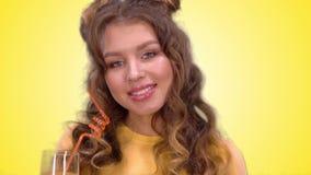 Uma moça bonita em uma veste amarela está bebendo o suco de uma palha e está sorrindo ao olhar na câmera filme