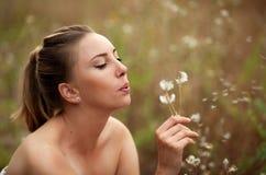 Uma moça bonita fez um desejo e sopros em um dente-de-leão fotografia de stock