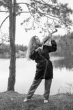 Uma moça bonita joga o violino na costa do lago Fotografia de Stock Royalty Free