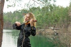 Uma moça bonita joga o violino na costa do lago Fotografia de Stock