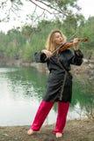 Uma moça bonita joga o violino na costa do lago Imagens de Stock Royalty Free