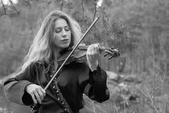 Uma moça bonita joga o violino na costa do lago Fotos de Stock
