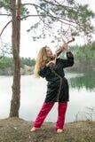 Uma moça bonita joga o violino na costa do lago Fotos de Stock Royalty Free