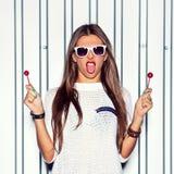 Uma moça bonita que está perto da parede está guardando o vermelho dois Fotografia de Stock Royalty Free