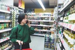 Uma moça chama o telefone e escolhe produtos no supermercado imagens de stock