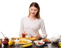 Uma moça coloca morangos em waffles belgas Foto de Stock Royalty Free