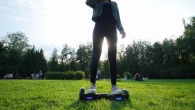 Uma moça com uma figura bonita que monta um giroscópio na grama no parque O sol está brilhando vídeos de arquivo