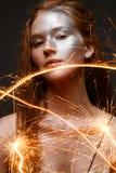 Uma moça com luzes de bengal e cabelo vermelho Um modelo bonito com pele de brilho e o brilho preparam ` S do ano novo e um feria fotografia de stock