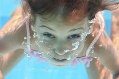 Uma moça com olhos abertos mergulha sob a água imagem de stock royalty free