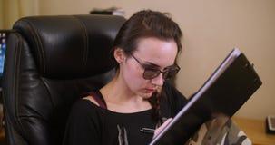 Uma moça com originais dos sinais dos vidros em casa video estoque