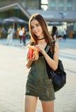 Uma moça com um cheeseburger e as fritadas em sua mão anda aro Foto de Stock Royalty Free