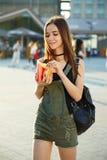 Uma moça com um cheeseburger e as fritadas em sua mão anda aro Foto de Stock