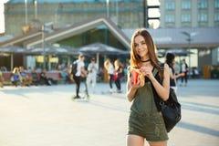 Uma moça com um cheeseburger e as fritadas em sua mão anda aro Fotografia de Stock