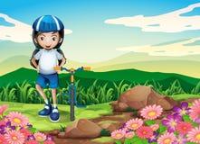 Uma moça com uma bicicleta que está perto da área rochosa Imagem de Stock