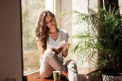 Uma moça consideravelmente magro com cabelo longo, equipamento ocasional vestindo, senta-se na soleira e lê-se um livro em um caf foto de stock