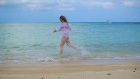 Uma moça corre ao longo da costa da praia, criando um pulverizador da água video estoque